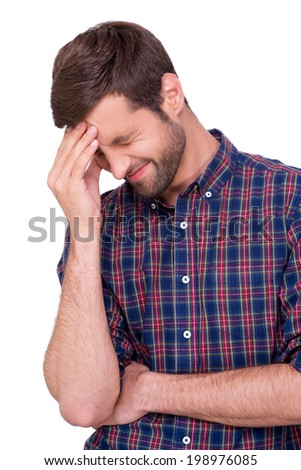Epic fail. Frustrated young man in casual shirt touching his forehead with hand and keeping eyes closed while standing isolated on white