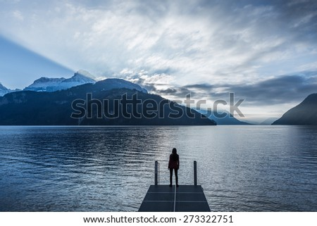 Epic landscape complete with a small woman figure. Mountain, lake and sky in bright colors of sunset - stock photo