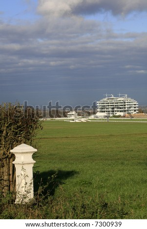 Epsom Grandstand and a milepost. - stock photo