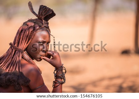 EPUPA, NAMIBIA - AUGUST 4: An unidentified Himba woman thoughful while tourists visit the the himba settlement on August 4, 2013 in Namibia - stock photo