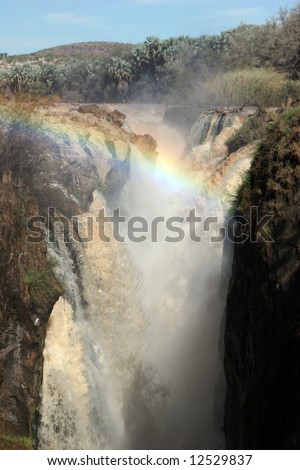 Epupa Waterfall plunging over cliff into deep ravine. Falls lie on the Kunene River, on the border of Angola and Namibia. - stock photo