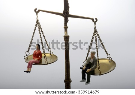 Equality between man and women sitting on a weighing balance - stock photo