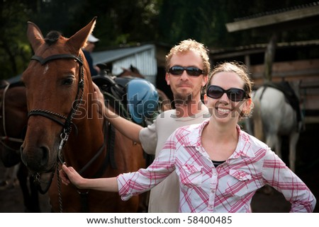 Equestrian couple posing on a horse ranch in Costa Rica - stock photo
