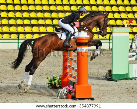 Equestrian girl horseback jumping obstacle  - stock photo