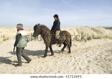 equestrian on horsback on beach with accompaniment