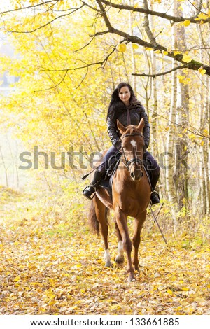 equestrian on horseback in autumnal nature - stock photo
