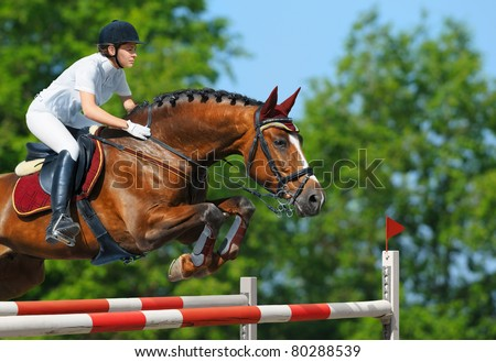 Equestrian sport - young woman jumping with bay horse - stock photo