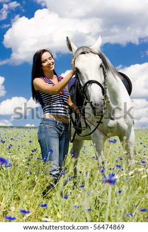 equestrian with a horse on meadow - stock photo