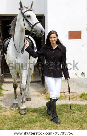 equestrian with horse at stable - stock photo