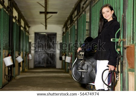 equestrian with saddle in a stable