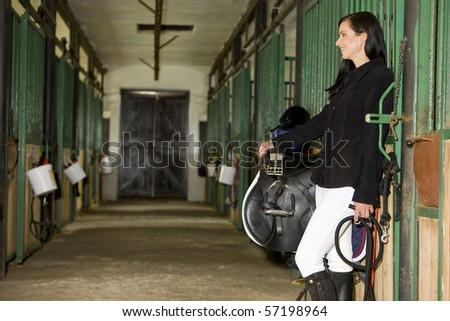 equestrian with saddle in a stable - stock photo