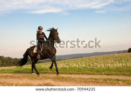 Equestrienne  rides at a gallop across the field.