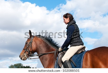 Equestrienne rides front of blue sky - stock photo