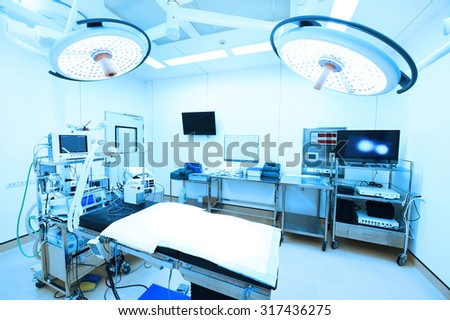 equipment and medical devices in modern operating room take with art lighting and blue filter  - stock photo