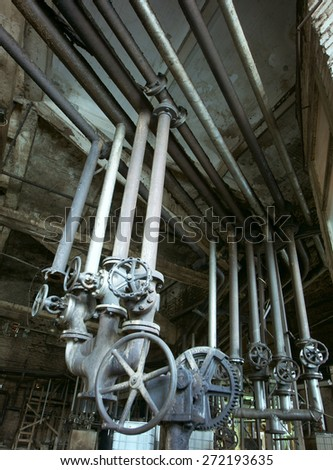Equipment, cables and piping as found inside of a old industrial power plant - stock photo