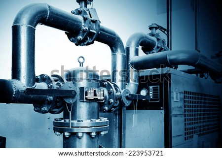 Equipment, cables and piping as found inside of industrial power plant - stock photo