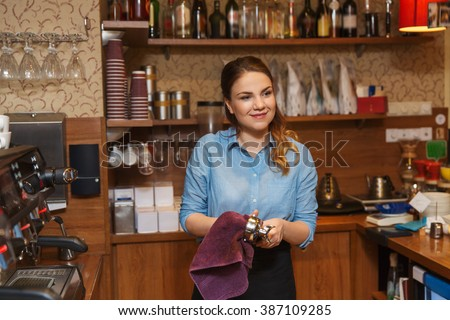 equipment, coffee shop, people and technology concept - happy barista woman cleaning espresso machine holder at restaurant bar