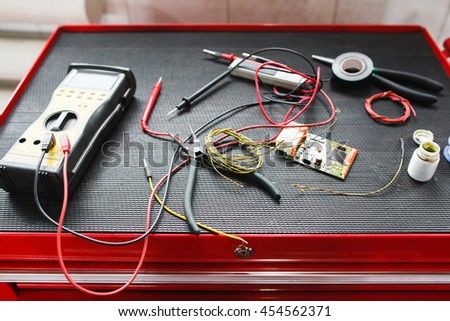 Equipment for electronic maintenance of car. Multimeter with necessary cables and connectors on electrician toolbox in garage, professional testing facilities - stock photo