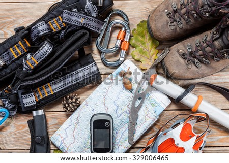 Equipment for mountaineering and hiking on wooden background.