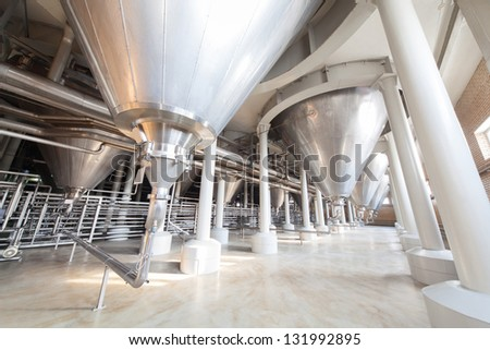Equipment for the brewery. Large tanks and many shiny tubes. - stock photo