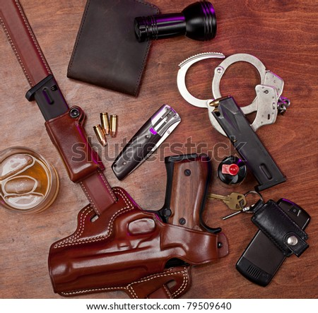 Equipment typically carried by a law enforcement officer, on a wooden table with a glass of whiskey. - stock photo
