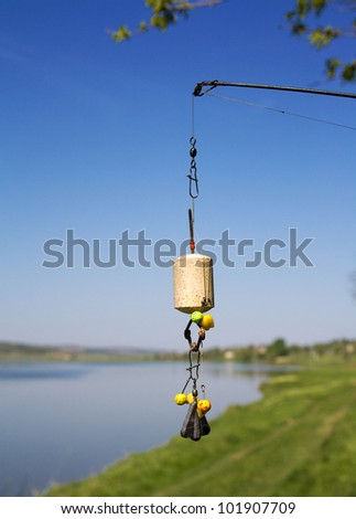 Equipped with a bait for carp, tehnoplankton attached to a fishing rod against the blue sky and the lake - stock photo