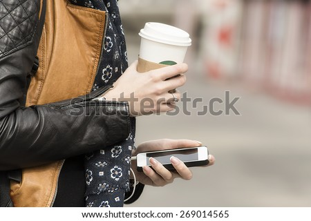Equipped with coffee and mobile phone in the city street. Concept of modern city life.   - stock photo