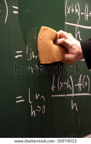 Erasing a blackboard written all over by math problem - stock photo
