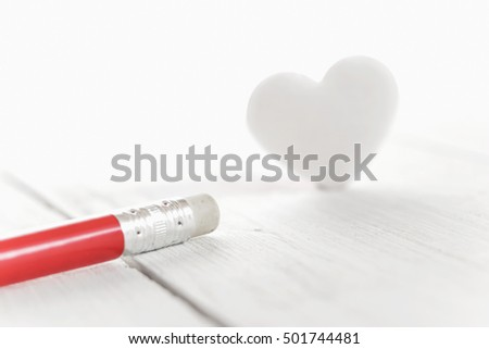 erasing passion from heart, eraser of pencil with heart shape on white background
