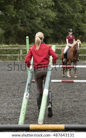 Erecting a jump in an outdoor riding school - September 2016 - Riding instructor carrying plastic poles to erect a fence in the riding school