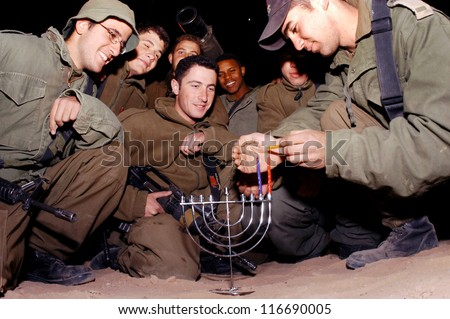 EREZ, ISRAEL- DECEMBER 16 2006:IDF soldiers lights Hanukkah candles near Kibbutz Erez. It commemorates the liberation of Jerusalem and the miracle of oil in the second Jewish Temple. - stock photo