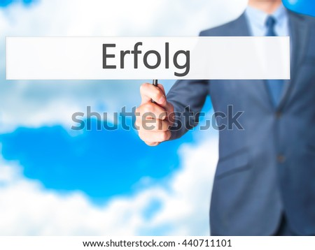 Erfolg (Success) - Businessman hand holding sign. Business, technology, internet concept. Stock Photo