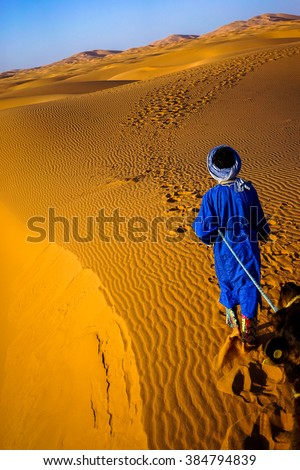 ERG CHEBBI, MOROCCO - CIRCA MAY 2015: A berber man is leading a camel into the sand dunes of Erg Chebbi in the Sahara Desert.  - stock photo