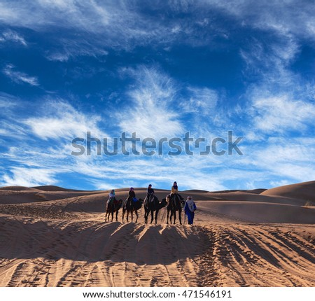 ERG CHEBBI, MOROCCO - JANUARY 6, 2014: Caravan crossing over dunes in desert in Western Sahara. Tourism is an important item in the economy of Morocco.