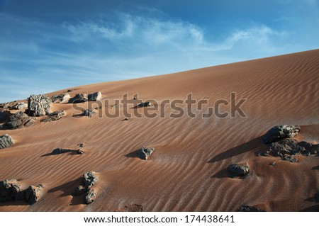 Erg Chebbi sandy dunes of Sahara Desert at the evening, Morocco. Dragon-like cloud. - stock photo