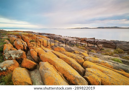 Eroded orange boulders cover the rocky coastline. - stock photo