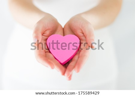 Eros - Hands Offering a heart, Studio shot using very shallow depth of field  - stock photo