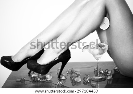Erotic alluring female legs in shoes on high heels and hand with half fresh juicy orange and cocktail with lime in glass black and white, horizontal picture - stock photo
