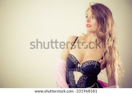 Erotic and provocative. Sensual attractive long haired female model posing in black sexy lingerie in studio. - stock photo