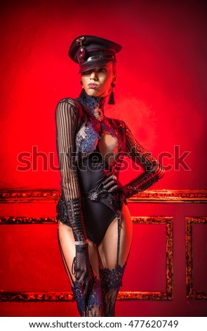 Erotic girl in military cap and lingerie with Stick in hand.