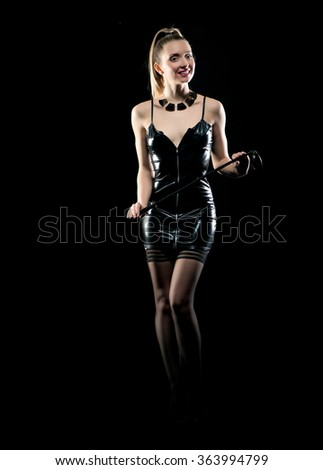 Erotic photo. Beautiful sexy blonde girl in black latex dress with a stack in the hands posing on a black background - stock photo