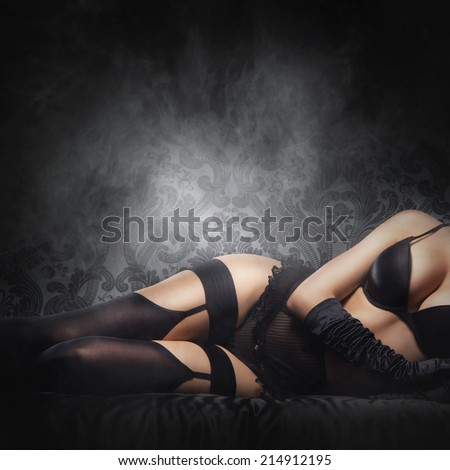 Erotic photo of young and beautiful woman in sexy underwear over smoky background - stock photo
