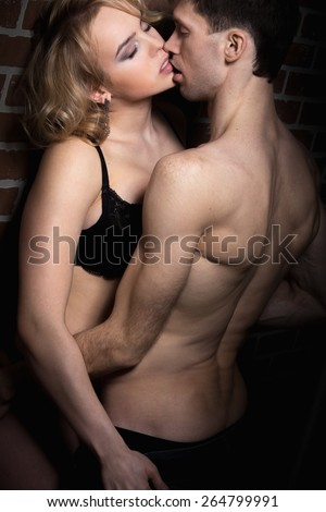 Erotic play of sexy young couple, half naked young man holding blond beautiful girl in black lingerie - stock photo