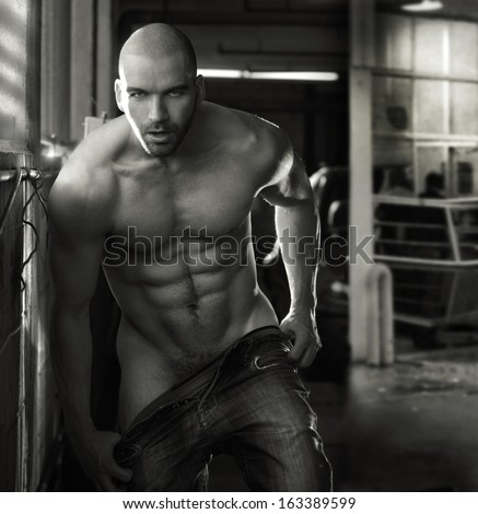 Erotic portrait of a muscular nude man in industrial garage setting - stock photo