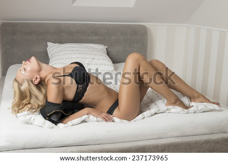 erotic portrait of allure blonde woman in provocative pose on bed with dark lingerie and open leather jacket. Perfect body.  - stock photo