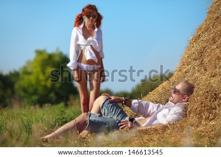 Erotic scene between brooding man lying on hayloft and his lovely girl - stock photo