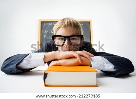 Erudite schoolboy sitting at the desk with textbook - stock photo
