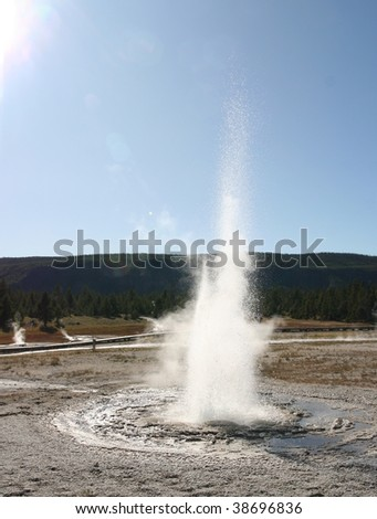 Eruption of a small geyser in Yellowstone National Park, with sun light from top left - stock photo