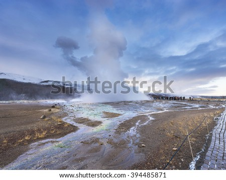 Eruption of Strokkur geyser in Iceland. Winter cold colors, sun lighting through the steam - stock photo