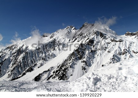 Erzbergspitze is  a mountain in the Austrian Alps with dramatic rocky spines, especially when set against fresh white snow.  In this image it is softened by gentle clouds on a clear blue sky. - stock photo